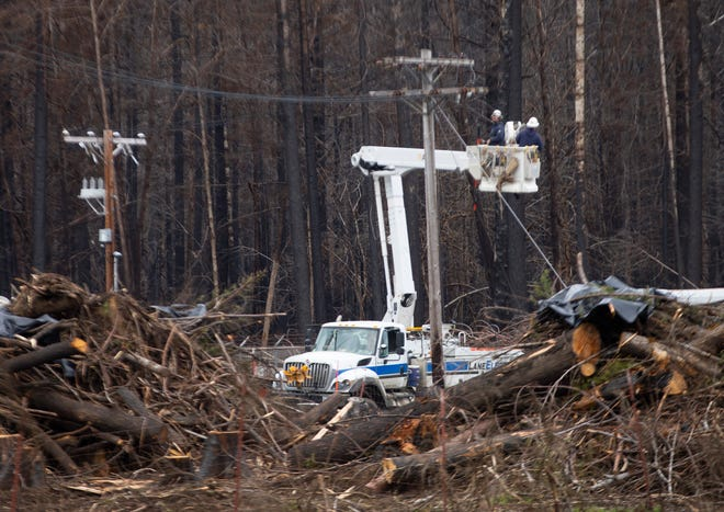 Crews from Lane Electric work on power lines along Highway 126 east of Springfield as work continues to replace infrustucture lost to the Holiday Farm Fire.
