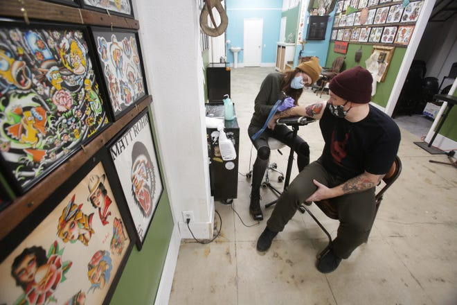 Tim Ruby of North Canton gets a tattoo from  Tatoo Artsist Margot LIbbon at  Eulogy Tatoo in downtown Canton.