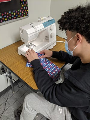 GlenOak High School senior Camren Lipkins sews the fabric for the Shopping Shield, which wraps around the handle of a shopping cart to help reduce the spread of germs. Lipkins and five other GlenOak seniors are selling the Shopping Shield as part of their Junior Achievement company project.