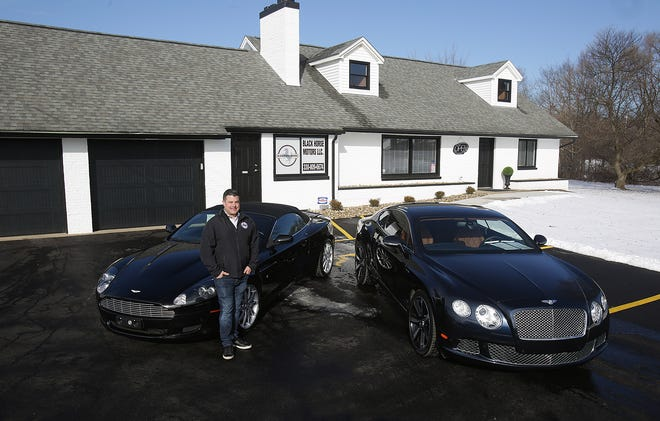 Phil Dimos, owner of Black Horse Motors in Jackson Township, stands next to a 2013 Bentley Continental GT LeMans Edition and a 2006 Aston Martin DB9. The cars are just a few of the high-end vehicles he has for sale on his lot. The business is at the former home of Fremont Montgomery, who for many years owned Monty's at the corner of Wales Avenue and Mudbrook Street NW.