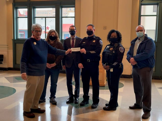 The Revs. Stephen Bowie and Julane Nease recently presented a $500 check at Rockford City Hall on behalf of Northwest Neighbors Inc. Mayor Tom McNamara and two deputy assistant chiefs were present to receive the check.