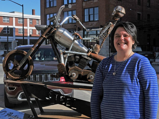 "Ann Corbett, of Salina, smiles after her husband's sculpture ""For The Love of Steel"" was named the 2020 People's Choice Award by the SculptureTour Committee in front of the Airgas Business Office, 253 N Santa Fe Ave, next to The Voo, on Friday. The late Sunny Corbett created the sculpture in six months in early mornings and during his lunch hours while working for Pestinger's Heating and Air Conditioning as a fabricator. ""I am glad that the community will be able to enjoy it for many years to come,"" said Ann Corbett."