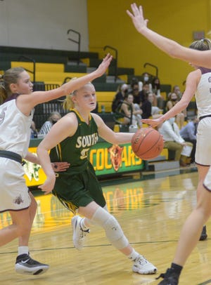 Salina South's Sydney Peterson (5) draws a foul while driving between a pair of Buhler defenders during Thursday's Salina Invitational Tournament game at the South gym.