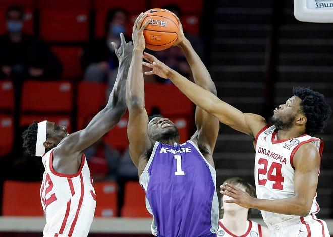 Kansas State center Kaosi Ezeagu grabs a rebound against Oklahoma's Kur Kuath (52) and Elijah Harkless during Tuesday's game in Norman, Okla.