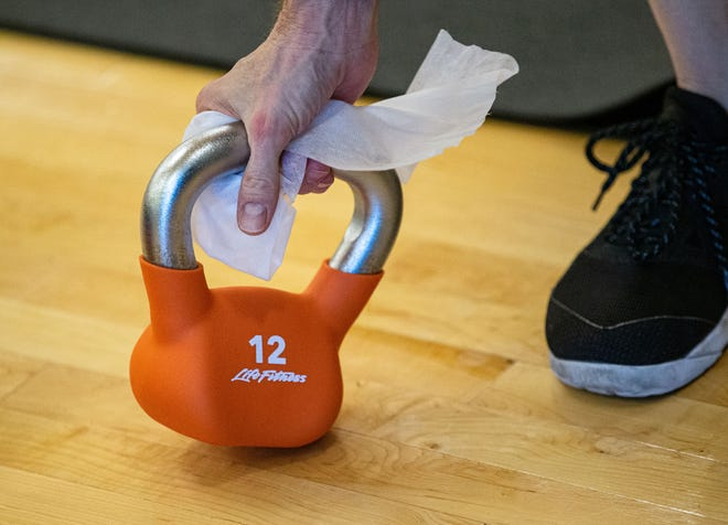 John Kerly uses a disinfectant wipe to clean off a kettle bell he used during an in-person Boot Camp group exercise class at the Downtown YMCA on Friday in Springfield. [Justin L. Fowler/The State Journal-Register]