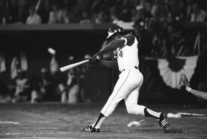 In this April 8, 1974, file photo, the Atlanta Braves' Hank Aaron hits his 715th career home run in Atlanta Stadium to break the all-time record set by Babe Ruth.  Aaron died early Friday, Jan. 22, 2021. He was 86. [JOE HOLLOWAY JR./AP FILE PHOTO]