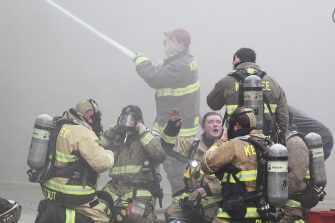 Kewanee firefighters regroup as they battled a fire at a building on Second Street last May. Two were injured fighting the blaze.