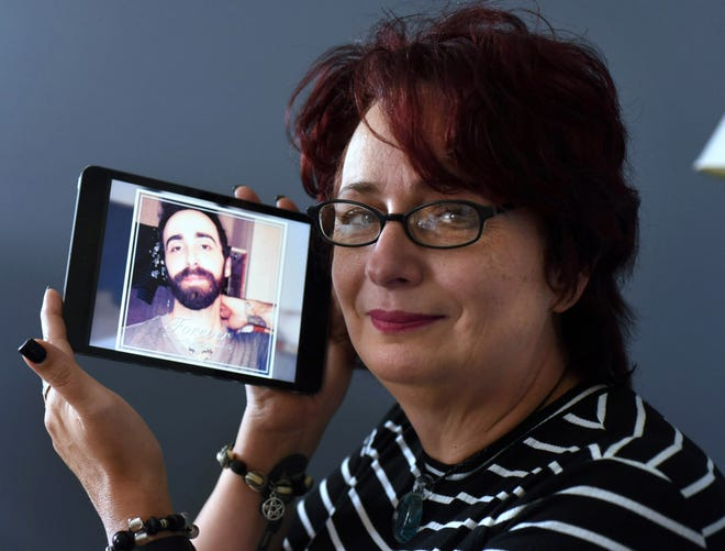 Cyndee Willis holds a picture of son Joshua Daughtry in Wilmington, N.C., Tuesday, October 10, 2017. Her son died last February from a heroin overdose and she has added his name and story to an online database map showing deaths from opioid overdoses.