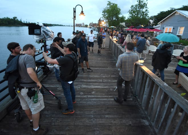 """Cast and crew from """"Words on Bathroom Walls"""" set up for filming along the Riverwalk in downtown Wilmington in 2018."""