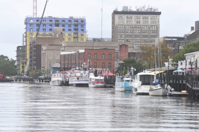 People walk along the Riverwalk in downtown Wilmington, N.C. Only a few boats permanently dock on the riverfront today, mostly for tourism purposes.