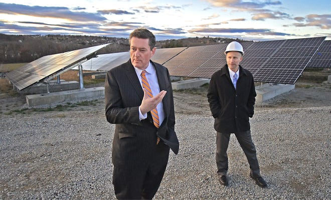 Worcester City Manager Ed Augustus, left, and John Odell, the city's energy and asset director, tour the new solar project at the Greenwood Street landfill site in 2016.
