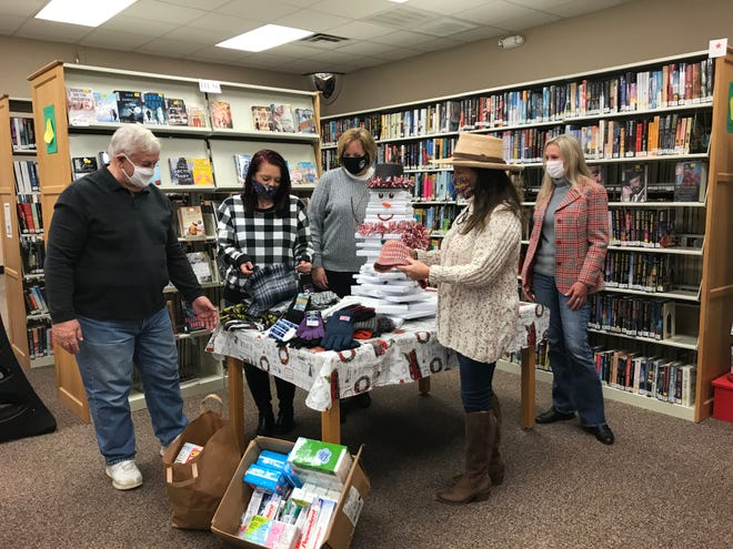 Southside library volunteer Bill Steinka, library director Sheila Watwood, assistant director Lynne Walker, Southside Mayor Dana Snyder, and mayor's assistant Elizabeth Mosley look over a small portion of the items donated to help the homeless.