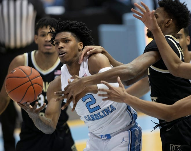 North Carolina's Caleb Love penetrates on a drive and is met by contact from Isaiah Mucius of Wake Forest during Wednesday night's game.