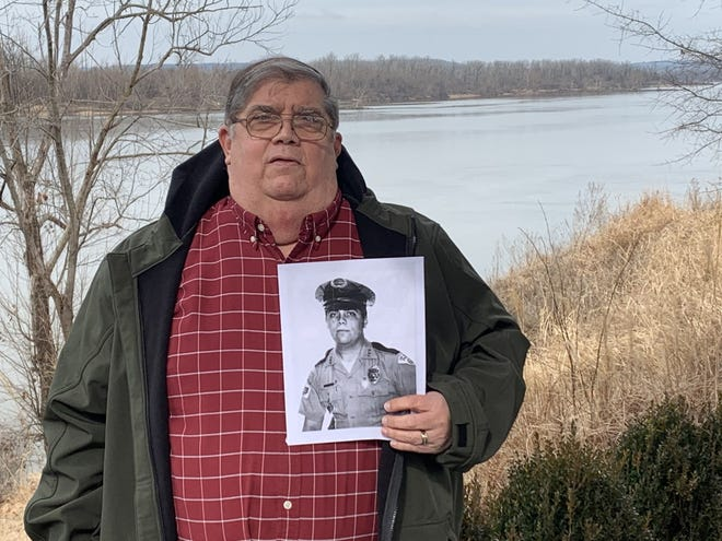Former Fort Smith police officer Kim Thompson, who served as an officer on the force from 1975-2000, shows a photo of himself in uniform at Harry E. Kelley River Park on Thursday, Jan. 21, 2021, in Fort Smith.