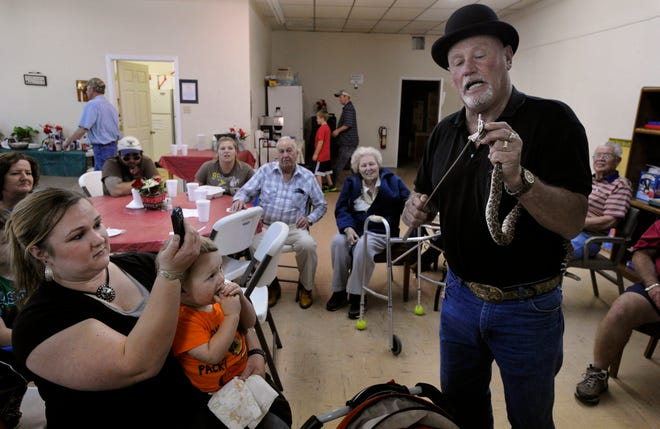Amber Wooten takes a photograph of snake handler Jackie Bibby while holding her two-year-old son J.T. during a fish fry fundraiser at the Cross Plains Senior Citizens Center Feb. 23, 2012. Bibby entertained diners with a pair of snakes, a boa and a rattlesnake. He refrained from any of his more well-known stunts like holding them in his mouth or sitting in a bathtub as they crawled over him.