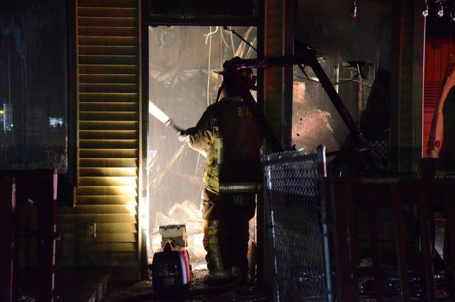 A firefighter battles the fire inside Hogzilla BBQ Smokehouse and Bar on Thursday.