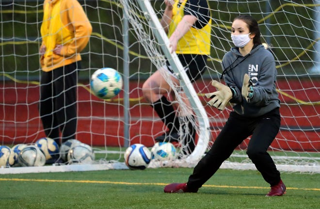 Olympic soccer goalie Maddie Puckett makes a save during practice at Olympic High School on Thursday, Jan. 21, 2021.