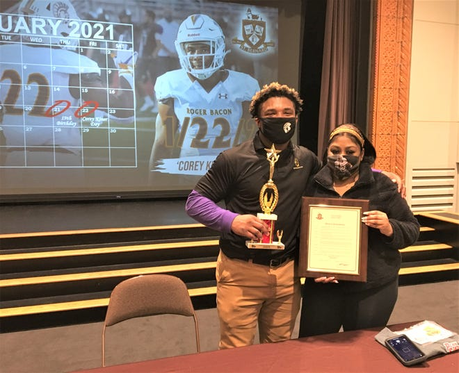 Roger Bacon senior Corey Kiner and his sister with a proclamation for Corey Kiner Day in St. Bernard and his award for Penn Station Athlete of the Month sponsored by WXIX-TV. Jan. 22, 2021.