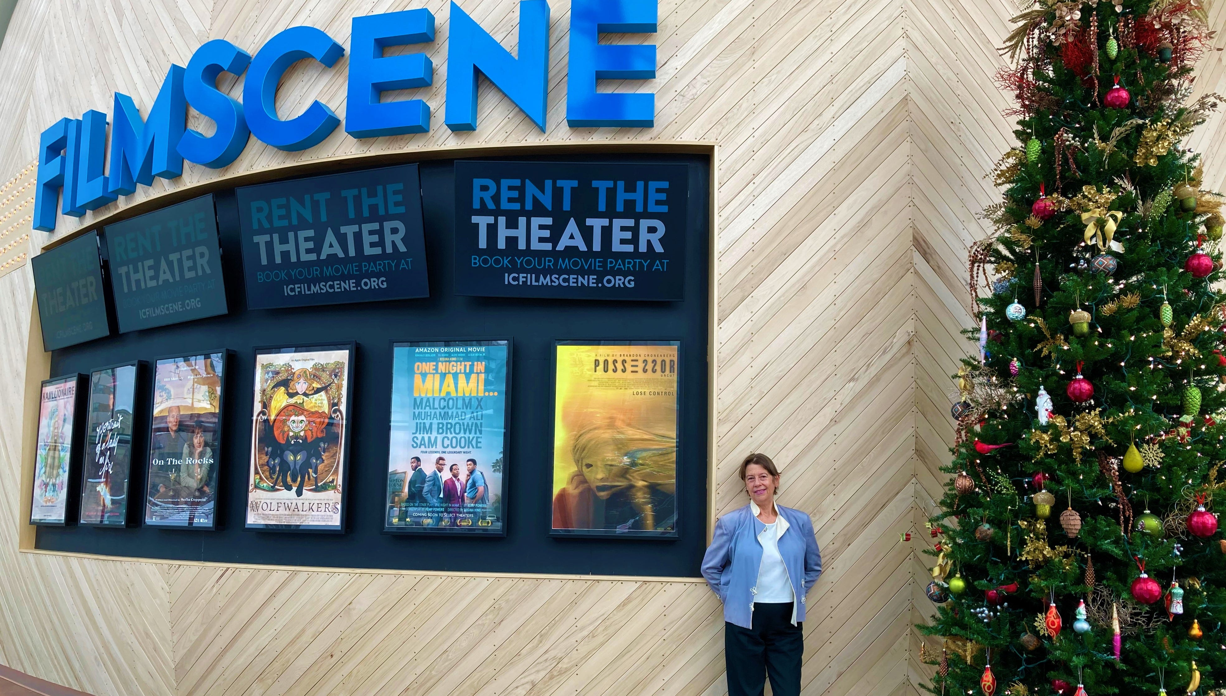 Mary Owen stands next to a line of posters in the lobby at Iowa City's FilmScene movie theater on Jan. 7, 2021.