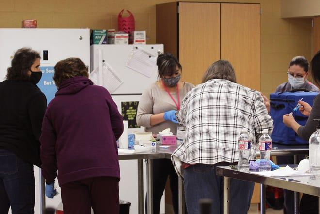 Cuatro enfermeras de la Escuela Independiente de Gadsden y dos empleados del Ministerio de Salud preparan las vacunas COVID-19 en la Escuela Secundaria de Gadsden el viernes 22 de enero de 2021.