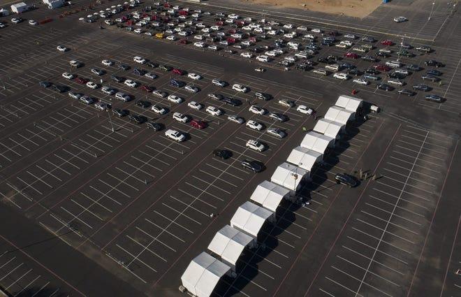 Los autos se alinean en el primer sitio de vacunación COVID-19 24/7 de Arizona en State Farm Stadium en Glendale el 12 de enero de 2021. El sitio debería facilitar alrededor de 6,000 vacunas por día cuando esté en pleno funcionamiento, según la directora de salud estatal, Dra. Cara Christ.