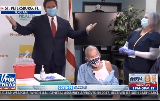 In this screenshot, Florida Gov. Ron DeSantis appears on Fox & Friends chaperoning 100-year-old Henry Sayler as he gets what DeSantis said may be the millionth senior COVID-19 vaccination in the state.