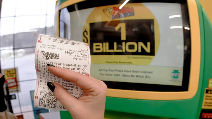 A patron, who did not want to give her name, shows the ticket she had just bought for the Mega Millions lottery drawing at the lottery ticket vending kiosk in a Smoker Friendly store, Friday, Jan. 22, 2021, in Cranberry Township, Pa. The jackpot for the Mega Millions lottery game has grown to $1 billion ahead of Friday night's drawing after more than four months without a winner. (AP Photo/Keith Srakocic) ORG XMIT: PAKS104