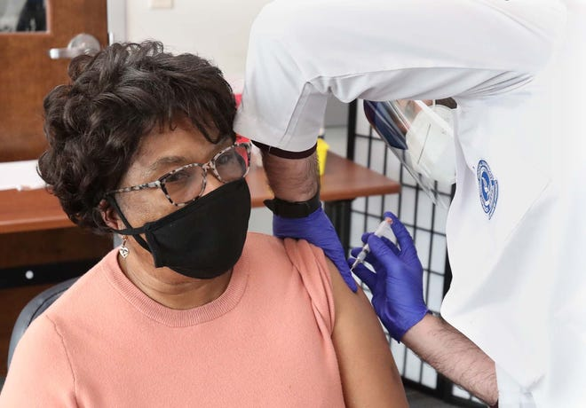 Wilhelmena Bentley of Akron gets vaccinated by Mohenad Rasoul, a third-year pharmacy student at Northeast Ohio Medical University, on Saturday at AxessPointe in Akron.
