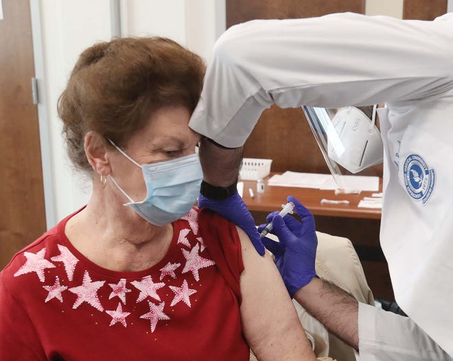 Julie Campbell is administered the first round of the COVID-19 vaccine by Mohenad Rasoul, a third-year pharmacy student at Northeast Ohio Medical University, Saturday at AxessPointe. Ohioans 75 and older are eligible to get the vaccine beginning this week.