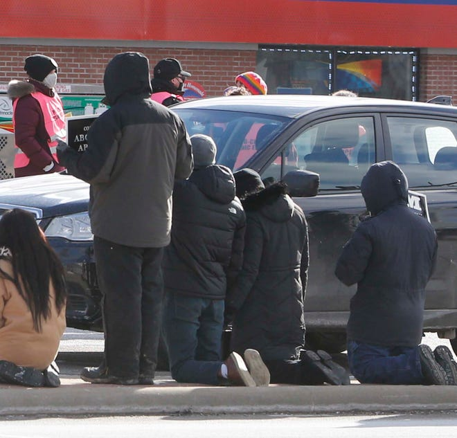 Demonstrators in January kneel and pray outside of the Northeast Ohio Women's Center in Cuyahoga Falls, where four protesters were arrested Friday and charged with trespassing.