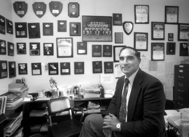 Barnstable High athletic director Steve Goveia in 1995 with many of the title plaques and trophies won by the school over the years. Goveia died at 83 years old from heart complications late last week.