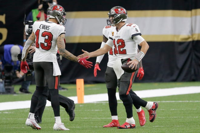 Tampa Bay quarterback Tom Brady celebrates a  touchdown with receiver Mike Evans against the Saints last Sunday.