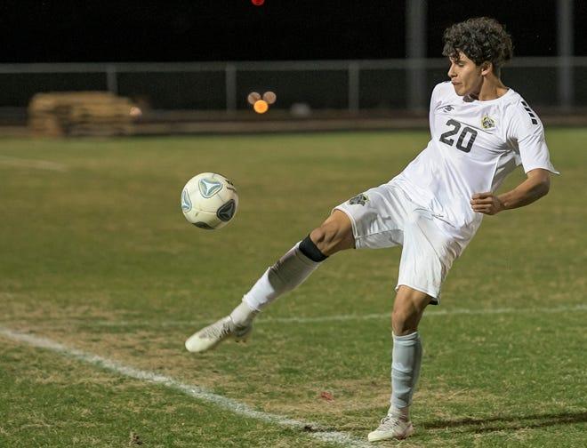 East Ridge's Rafael Luyo (20) kicks the ball during Friday's match against Lake Minneola in Minneola. [PAUL RYAN / CORRESPONDENT]