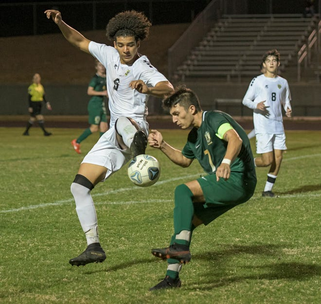 East Ridge's Eric Suarez (6) tries to gain possession as Lake Minneola's Israel Luna (7) defends during Friday's game at Lake Minneola. East Ridge won the 22nd meeting between the teams, 1-0. [PAUL RYAN / CORRESPONDENT]