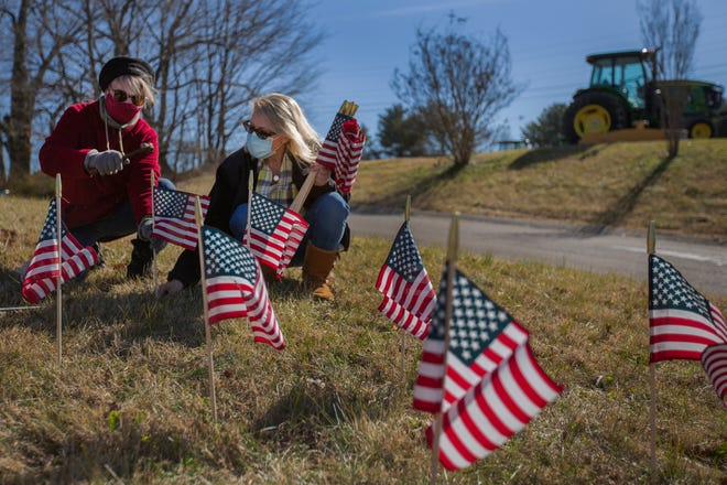 Judith Amatore, left, and Rhonda Westerfield, right, place flags along U.S. 31 in recognition of the Maury County residents, who have died from the COVID-19 pandemic. A group of local residents gathered in Columbia, Tenn., to create the display on Saturday, Jan. 23, 2020.