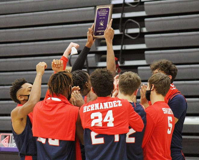 Truman players hoist the championship plaque of the 71st annual North Kansas City Invitational after holding off Raymoire-Peculiar for a 43-40 win in the final Friday night.