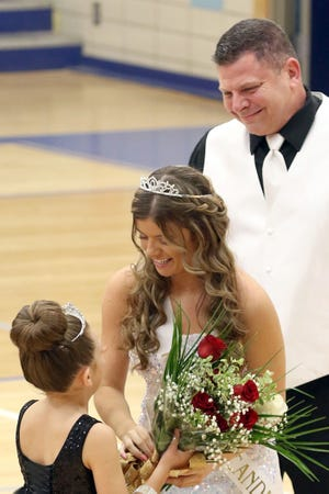 Notre Dame's 2021 Homecoming queen Kerrigan Belger is congratulated by Notre Dame's junior princess as Jim Belgers look on Friday night at Father Minett Gymnasium in Burlington.
