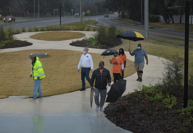Cosmo community residents walk with Jacksonville City Council member Al Ferraro on the winding paved path in the newly created Freedom Park in East Arlington. Located at the junction of Ft. Caroline and McCormick roads, the park will highlight the story of the Cosmo community, which was founded by freed slaves, and also honor veterans who have post traumatic stress disorder.