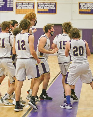 The Monty Tech Bulldogs swarm around Fred Fairbanks (15) to celebrate the senior's buzzer-beating 3-pointer lifted the home team to a thrilling 36-35 victory over the Trivium Eagles, Friday night, at Bulldog Gym in Fitchburg.