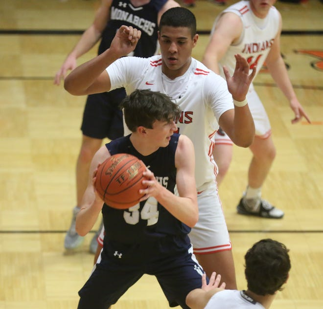 TMP-Marian's Dylan Werth is guarded by Hoxie 7-footer Harlan Obioha on Friday in the MCL Tournament semifinals at Ellis.