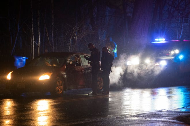 Masked Maynard police officers talk with the driver during a traffic stop in town, Jan. 14, 2021.