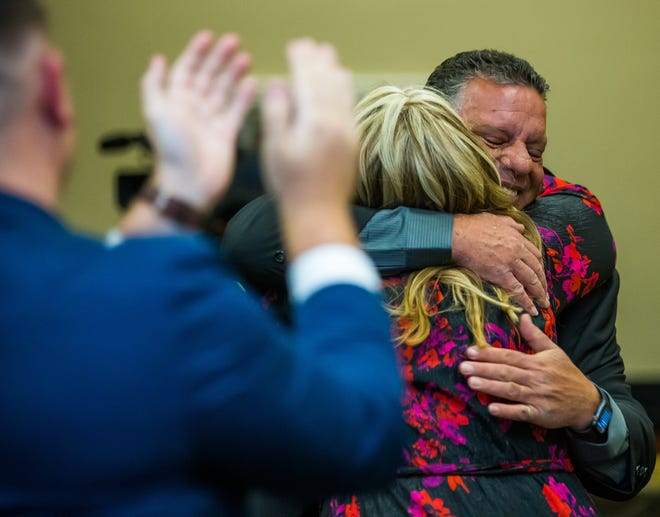 Tony Fernandez hugs his wife, Christine, an MCPSonline kindergarten and first-grade teacher at Shady Hill Elementary School, was named 2021 Teacher of the Year at the 31st annual Golden Apple Gala on Friday night. [Doug Engle/Ocala Star Banner]2021