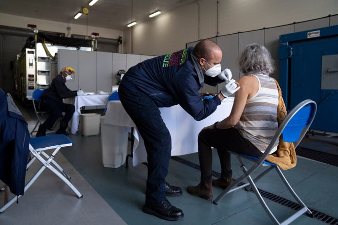 Firefighter/paramedic John Kostyo Jr., gives a resident a COVID-19 vaccination at the Tequesta Fire Department on Jan. 15. Florida Democrats are calling on GOP Gov. Ron DeSantis to do more to expedite vaccinations to state residents. GREG LOVETT/PALM BEACH POST