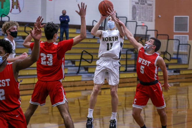Cranston West's Michael Paquette and William Nebus (23) defend North Kingstown's Will Masse as he takes a jump shot.  Providence Journal / David DelPoio]