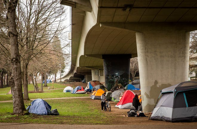 "A man walks his bike along an encampment underneath the I-105 bridge during an overcast day in January. The City of Eugene has temporarily allowed ""urban camping"" to avoid dispersing campers during the COVID-19 pandemic."