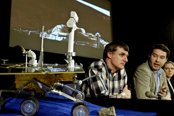 Members of the Mars Exploration Rovers team, Steve Squyres, left, principal investigator, Jim Bell, panoramic camera team leader, center, and Jennifer Trosper, mission manager, attend a news briefing at NASA's Jet Propulsion Laboratory on Jan. 26, 2004, in Pasadena, California. In the background is the first color postcard, a mosaic of 24 separate frames, taken by the rover Opportunity's panoramic camera. Opportunity sent its first pictures of Mars to Earth on Jan. 25, 2004, showing a surface smooth and dark red in some places, and strewn with fragmented slabs of light bedrock in others.