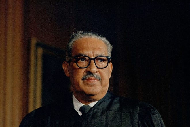 Thurgood Marshall, the first black associate justice of the U.S. Supreme Court, is photographed on his first day in court wearing judicial robes, Oct. 2, 1967. Marshall died on this day in 1993.
