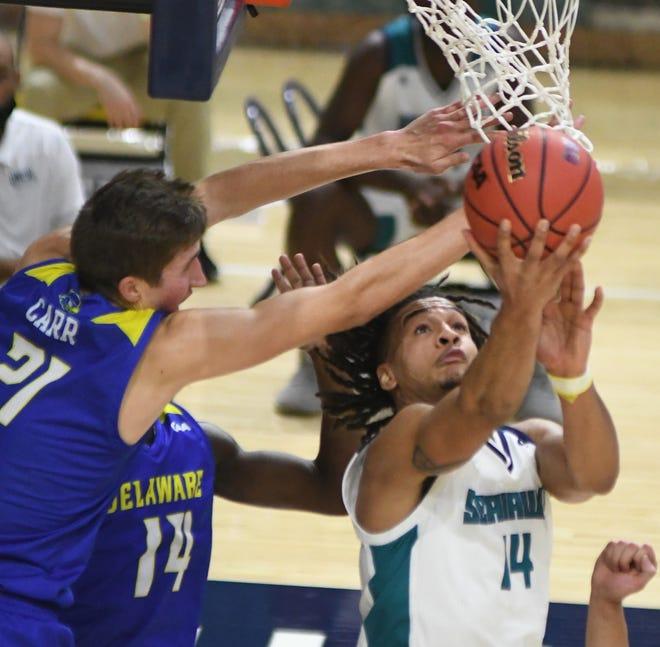 UNCW's Joe Pridgen shoots under the basket against Delaware at Trask Coliseum in Wilmington, N.C., Saturday, January 23, 2021.   [MATT BORN/STARNEWS]