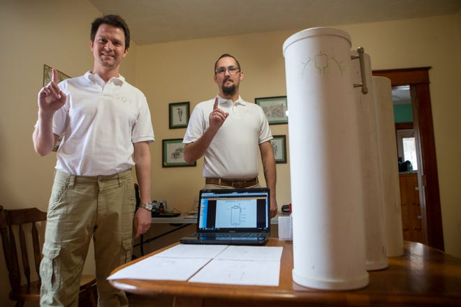 Alex Stokes, left, and Seth Sheperd, right, pose next to their patented Earthgenuity Composting System on Saturday afternoon inside their home office in Topeka. The duo hopes to help alleviate the stress of composting with their new system.