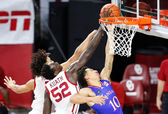 Kansas basketball's Jalen Wilson, right, has a shot blocked by Oklahoma's Kur Kuath during Saturday's game at Lloyd Noble Center in Norman, Okla. The No. 9-ranked Jayhawks fell 75-68 for their third straight conference defeat.